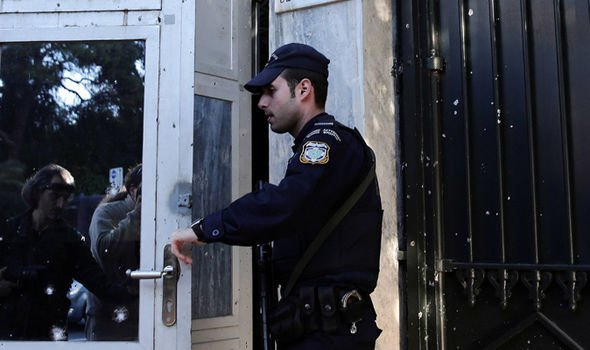 Police examines the damage done to the booth at the French Embassy in Athens