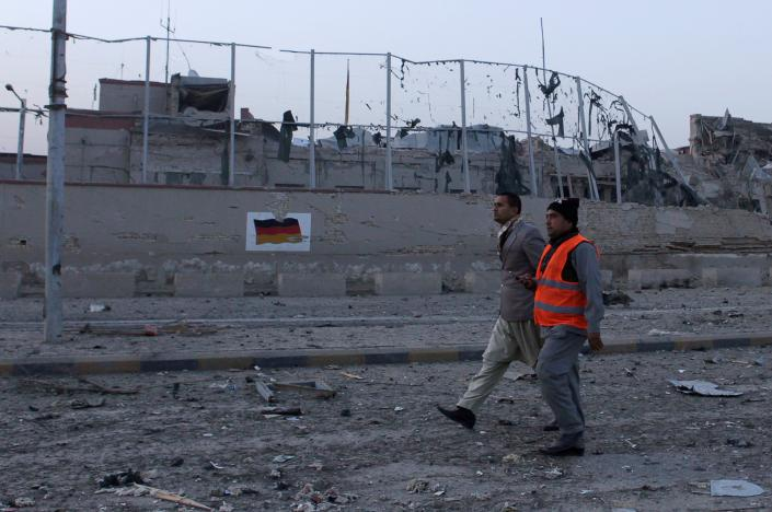 An Afghan municipality worker walks on the road with another man in front of the German consulate after a blast in Mazar-i-Sharif, Afghanistan November 11, 2016. REUTERS/Anil Usyan
